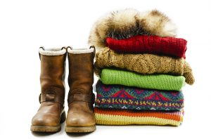 Winter boots, cap and stack of various sweaters. Winter style