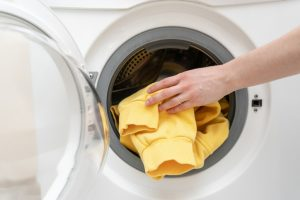Concept of laundry process. Cropped and close up photo of woman hand put clothes in white modern washing machine. She standing inside light flat interior