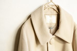 beige wool coat hanging on clothes hanger on white background